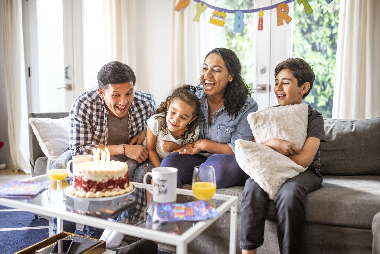 Happy family celebrating a birthday in the living room with cake