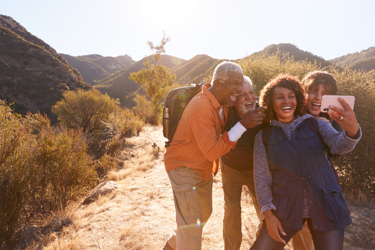 Best friends posing for selfie as they hike along trail in countryside together