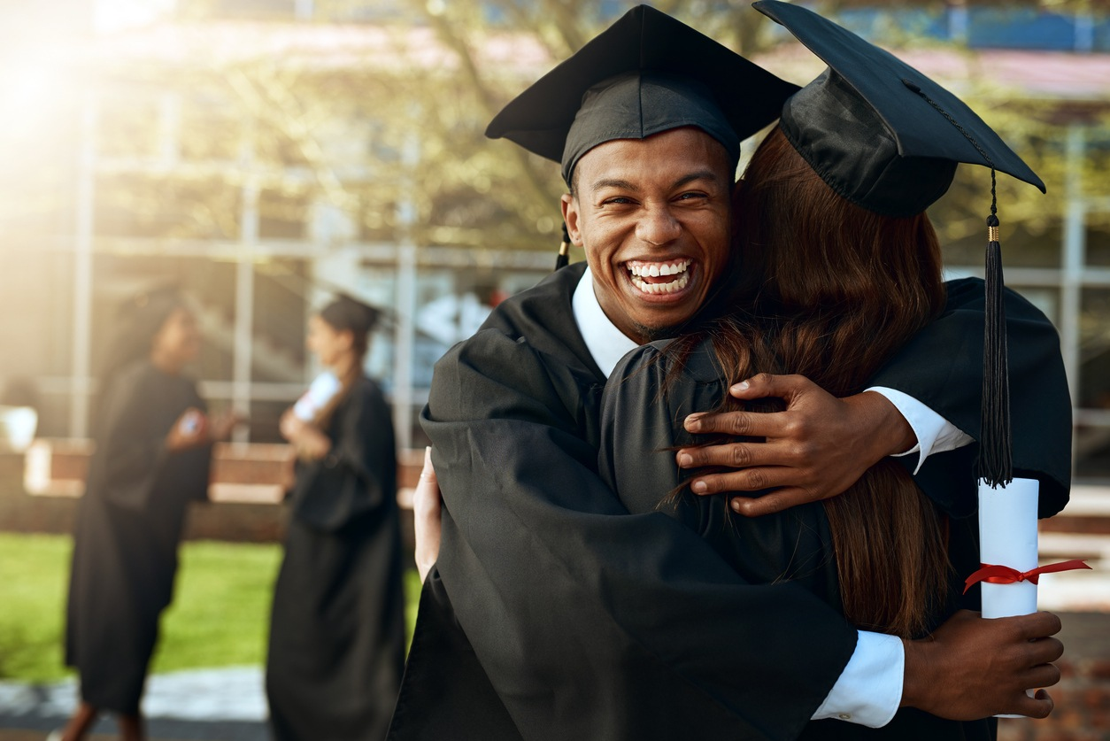 Portrait of a happy young man and woman hugging on graduation day